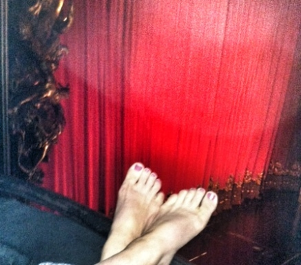 barefeet hanging over the edge of the box seats